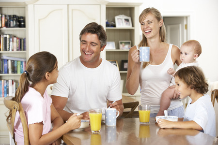 5 10 year old girl: Family Having Breakfast In Kitchen Together Stock Photo