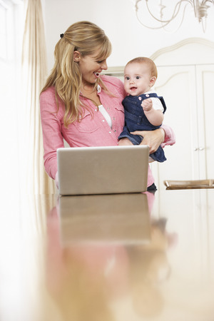 whilst: Mother Holding Baby Daughter Whilst Using Laptop Stock Photo