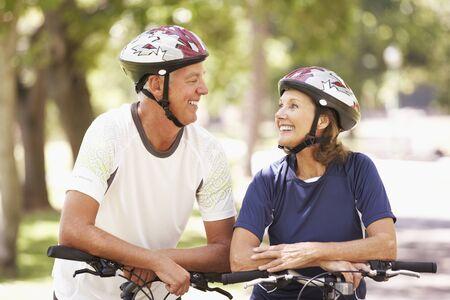 ciclismo: Retrato de pareja madura en paseo del ciclo a trav�s de parque