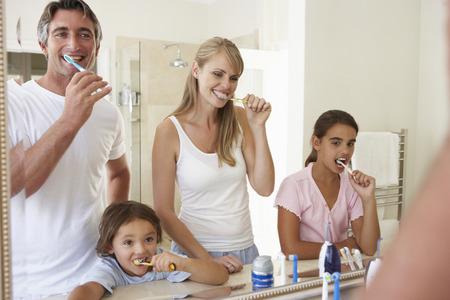dientes: Dientes de cepillado de la familia en cuarto de baño Espejo Foto de archivo