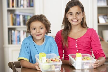 5 10 year old girl: Two Children With Healthy Lunchboxes In Kitchen Stock Photo