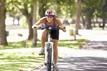 outdoor pursuit: Woman Cycling Through Park Stock Photo