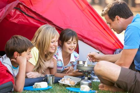niños cocinando: Familia Prepara el desayuno en acampada