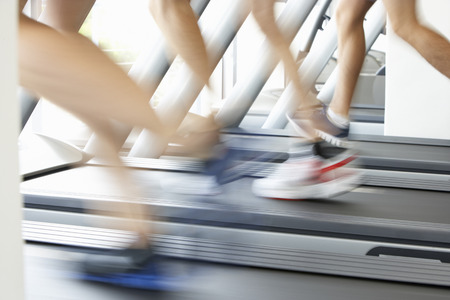 fast foot: Close Up Of 3 Runners Feet On Running Machine In Gym Stock Photo