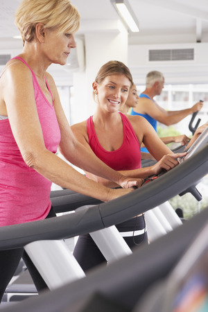 encouraged: Woman On Running Machine In Gym Encouraged By Personal Trainer