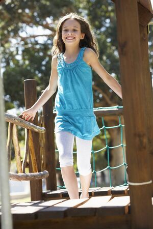 climbing frame: Young Girl Having Fun On Climbing Frame Stock Photo