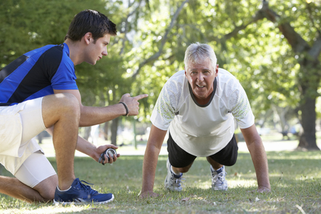 personal trainer: Senior Man Working With Personal Trainer In Park