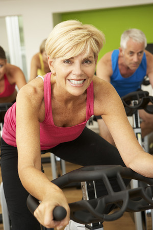 Woman Taking Part In Spinning Class In Gym