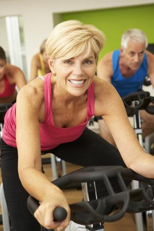 clase media: Mujer que toma parte en clase de giro en gimnasia Foto de archivo