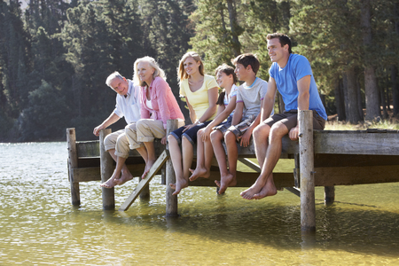 jetty: Three Generation Family Sitting On Wooden Jetty Looking Out Over Lake Stock Photo