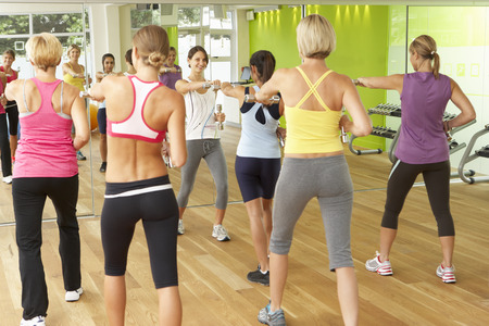 keep fit: Women Taking Part In Gym Fitness Class Using Weights