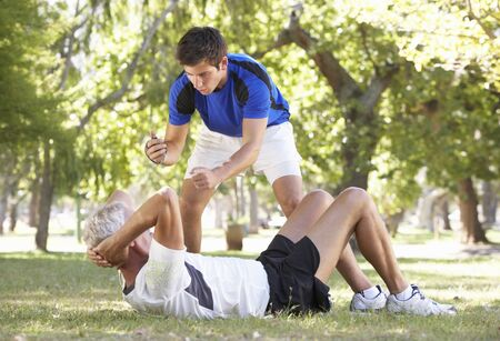 sit ups: Senior Man Working With Personal Trainer In Park