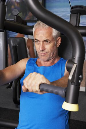 Weights: Middle Aged Man Using Weights Machine In Gym