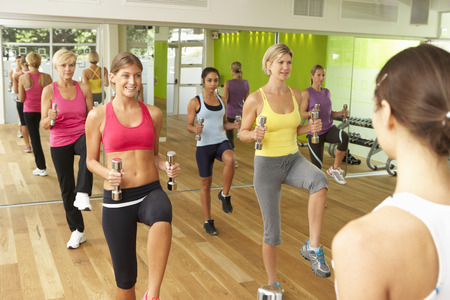 motivating: Women Taking Part In Gym Fitness Class Using Weights