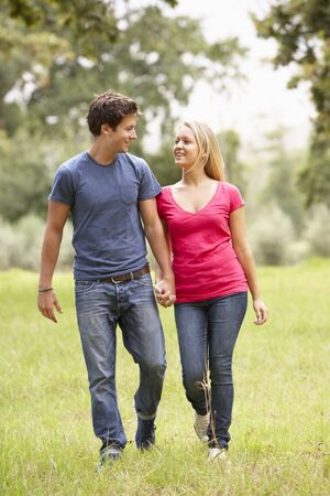 love hands: Romantic Young Couple Walking Through Countryside Stock Photo