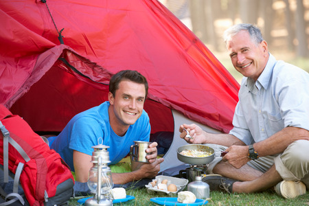 grown ups: Father And Adult Son Cooking Breakfast On Camping Holiday