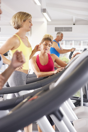 personal trainer: Woman On Running Machine In Gym Encouraged By Personal Trainer