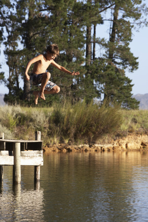 swimshorts: Boy Jumping From Jetty Into Lake Stock Photo