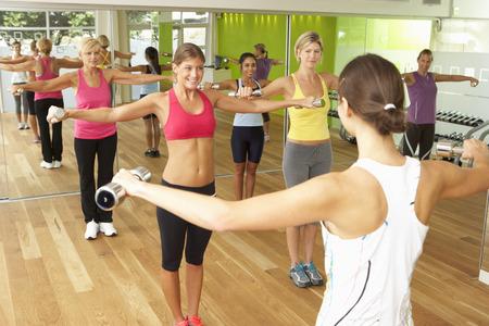 clase media: Las mujeres que participan en Gym Fitness Class Usando Pesas