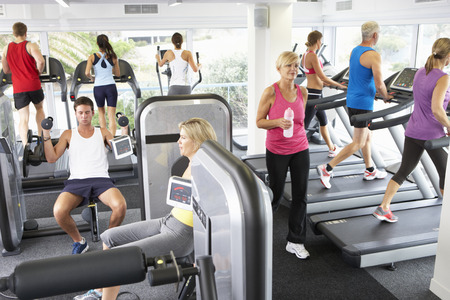 exercise equipment: Elevated View Of Busy Gym With People Exercising On Machines