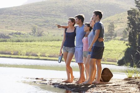 personas de pie: Grupo de jóvenes personas de pie en la orilla de lago que salpica el agua