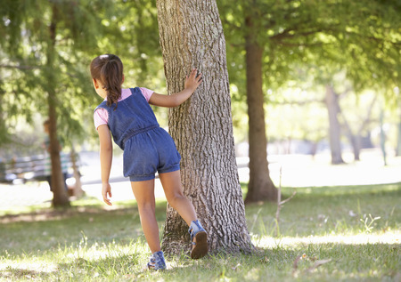 Child Playing Hide And Seek In Park