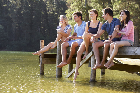 jetty: Group Of Young Friends Sitting On Wooden Jetty Looking Out Over Lake Stock Photo