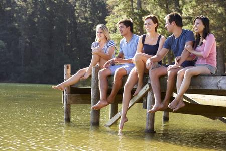 grupos de personas: Grupo de jóvenes amigos que se sienta en el embarcadero de madera que mira hacia fuera sobre el lago
