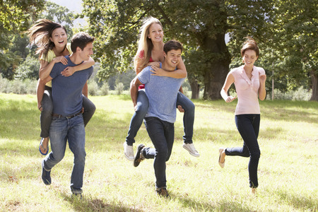 asian adult: Group Of Young Friends Running Through Countryside Stock Photo