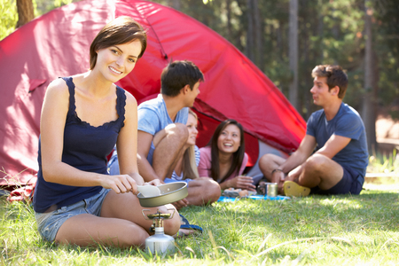 Young Woman Cooking Breakfast For Friends On Camping Holiday Stock Photo