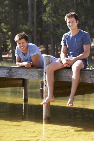 two men: Two Men Sitting On Wooden Jetty Looking Out Over Lake Stock Photo