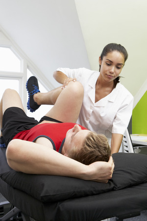 physiotherapist: Sports Physiotherapist Treating Male Client