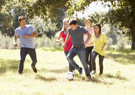 women playing soccer: Group Of Young Friends Playing Soccer In Countryside Stock Photo