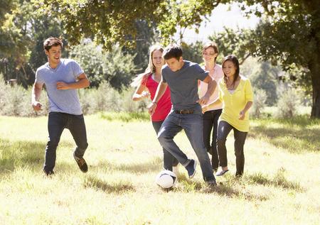 jugando futbol: Grupo de jóvenes amigos jugando al fútbol en Campo Foto de archivo