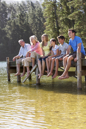 Three Generation Family Sitting On Wooden Jetty Looking Out Over Lake 스톡 콘텐츠