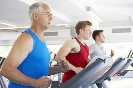 keeping fit: Group Of Men Using Running Machines In Gym