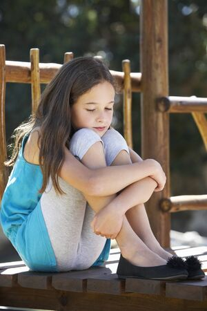 11 year old girl: Sad Young Girl Sitting On Climbing Frame Stock Photo