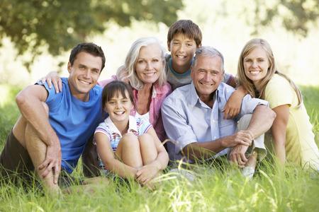 Familia de tres generaciones que se relaja en campo del verano