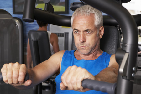 keeping fit: Middle Aged Man Using Weights Machine In Gym
