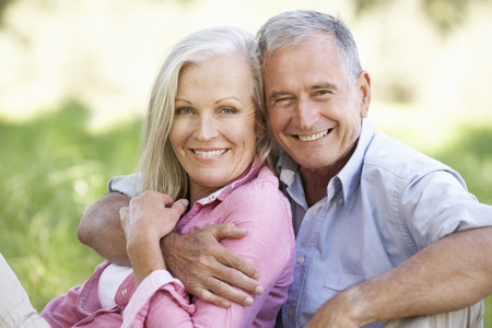 Senior Couple Relaxing In Sunny Summer Field Banque d'images