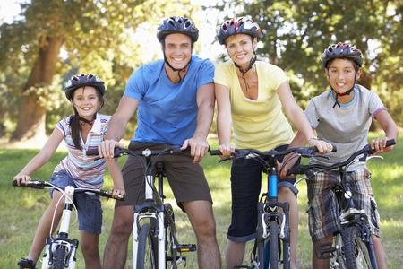 andando en bicicleta: Familia en paseo del ciclo En Campo Foto de archivo