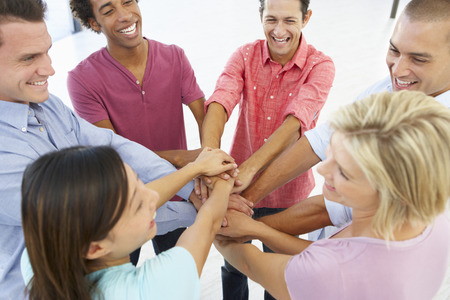 team success: Close Up Of Business People Joining Hands In Team Building Exercise Stock Photo