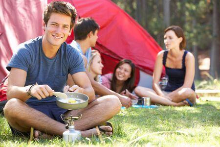 若い友人のためにキャンプの休暇の料理朝食を男します。 写真素材