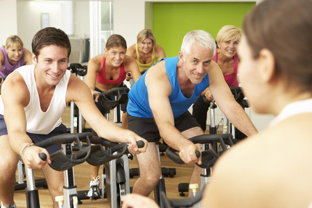 exercise bike: Group Taking Part In Spinning Class In Gym