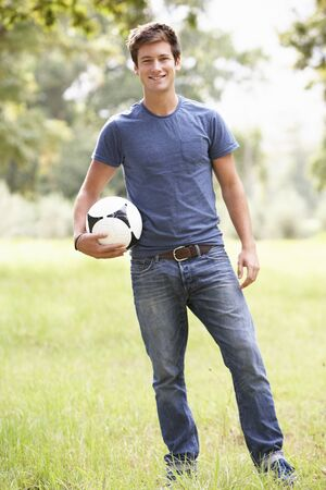 young adult men: Young Man Holding Soccer Ball In Countryside