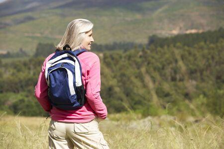 trekker: Senior Woman On Hike Through Beautiful Countryside