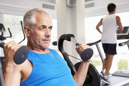 middle aged man: Man Using Weights Machine With Runner On Treadmill In Background Stock Photo