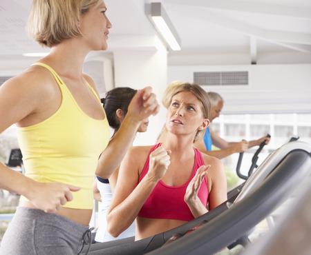 motivating: Woman On Running Machine In Gym Encouraged By Personal Trainer