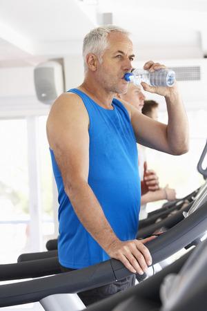 man drinking water: Man On Running Machine In Gym Drinking Water