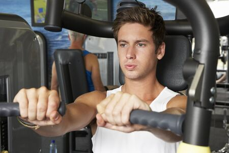 young man: Young Man Using Weights Machine In Gym